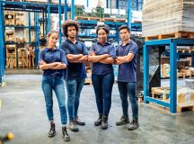 Group portrait of staff at distribution warehouse. Warehouse team standing with arms crossed in factory.
